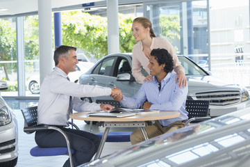Salesman and couple shaking hands at table in car dealership showroom