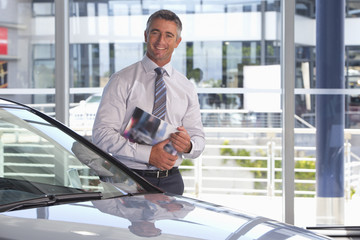 Portrait of smiling salesman holding brochure in car dealership showroom