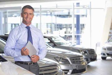 Portrait of smiling salesman holding digital tablet in car dealership showroom