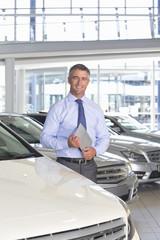 Portrait of smiling salesman holding digital tablet in car dealership showroom