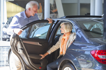 Smiling couple looking at car in car dealership showroom