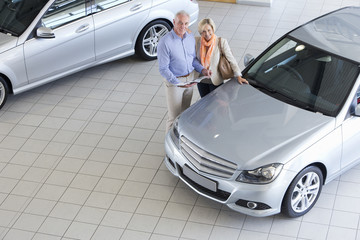 Portrait of smiling couple with brochure looking at car in car dealership showroom
