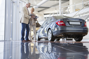 Couple with brochure looking at car in car dealership showroom