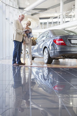 Couple looking at brochure next to car in car dealership showroom
