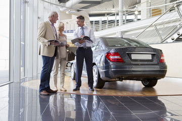 Salesman and couple with brochures next to car in car dealership showroom