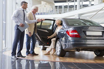 Salesman and couple looking at car in car dealership showroom