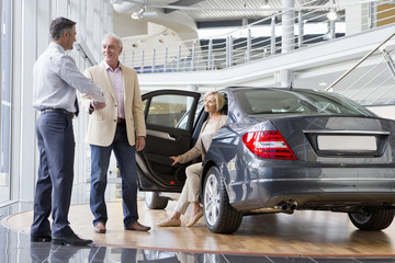 Salesman shaking hands with customer next to car in car dealership showroom