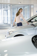 Customer looking at car in car dealership showroom