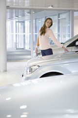 Portrait of smiling customer looking at car in car dealership showroom