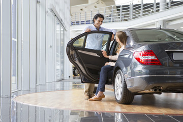 Couple looking at car in car dealership showroom