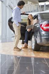 Couple looking at brochure in car dealership showroom