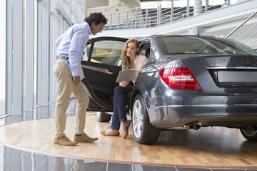 Couple looking at brochure in car dealership showroom