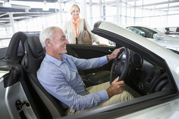 Smiling couple looking at convertible in car dealership showroom