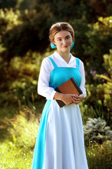 sweet girl with a book in his hands in a long azure dress