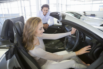 Couple looking at convertible in car dealership showroom