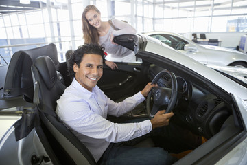 Portrait of smiling couple looking at convertible in car dealership showroom