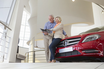 Couple looking at brochure and leaning on automobile hood in car dealership showroom