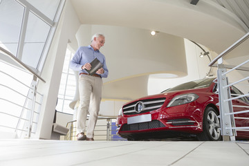 Man looking at car in car dealership showroom