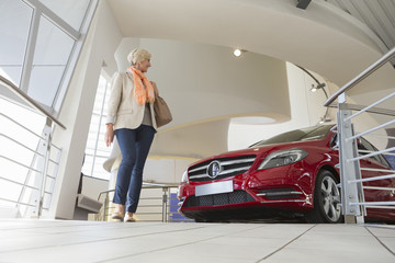 Woman looking at car in car dealership showroom