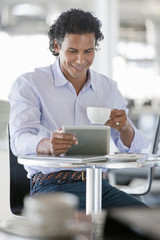Smiling man drinking coffee and using digital tablet at cafe table