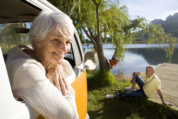 Portrait of senior woman leaning from window of camper van by lake, senior man on jetty in background