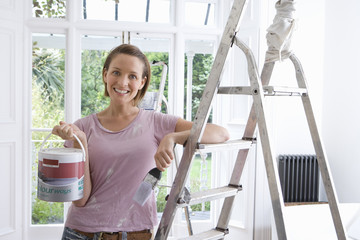 20's woman home decorating indoors with paint, brush and ladder ,