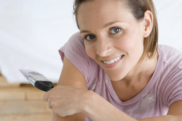 Young woman home decorating indoors with paintbrush, smiling, portrait, close-up,