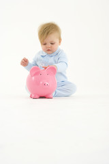 Baby boy (3-6 months) playing with piggy bank