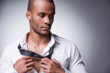 Taking his necktie away.