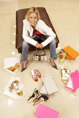 Blonde woman trying on different pairs of high heels in shoe shop, portrait, elevated view