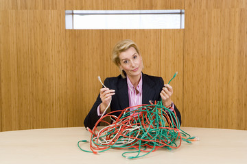 Businesswoman at table with bunch of tangled cable leads, holding up two ends, portrait