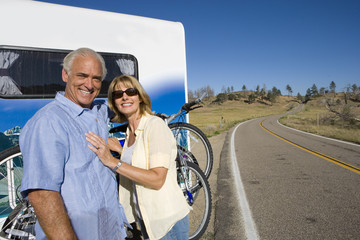Mature couple by bicycles on back of motor home, smiling, portrait