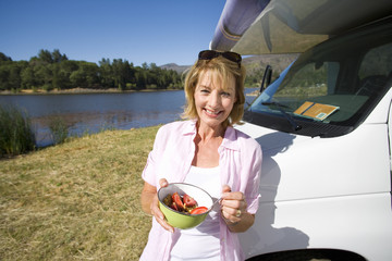 Mature woman with breakfast bowl by motor home and lake, smiling, portrait
