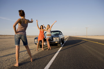 Young woman taking photograph of friends by car on open road, low angle view