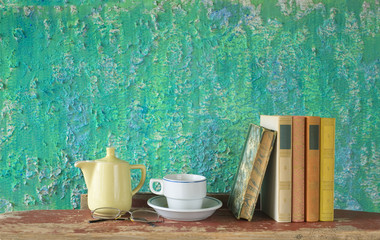 row of books with coffee cup, coffee pot and spectacles