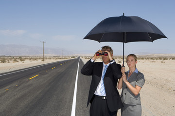 Businessman on open road in desert using binoculars by businesswoman with umbrella