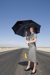 Businesswoman on open road in desert with umbrella, low angle view