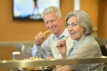 Mature couple eating french fries