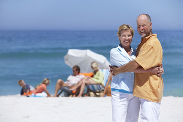 Senior couple embracing on beach, smiling, family near sea, focus on foreground, portrait