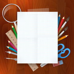 blank paper with school supplies tools on wood background