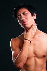 Young man suffering from neck pain on black background