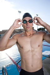Young man adjusting goggles next to swimming pool