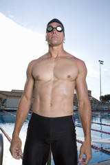 Young man in goggles and swim trunks next to swimming pool