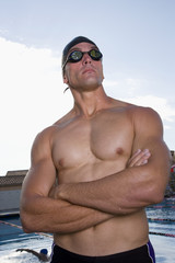 Young man with goggles and arms crossed next to swimming pool