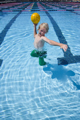 Young boy playing with ball in swimming pool