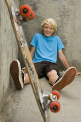Boy (11-13) with skateboard against wall, smiling, portrait