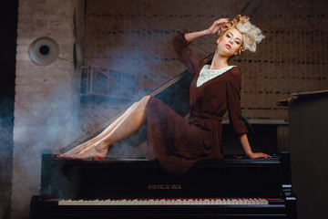 Model in a brown dress lying on the piano
