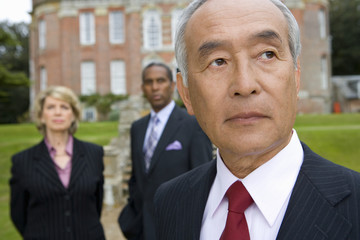 Mature businessman and colleagues by manor house, close-up