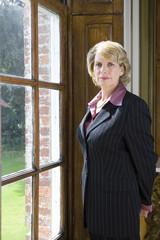 Mature businesswoman looking out window, portrait