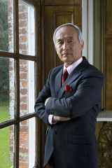 Mature businessman by window, arms crossed, portrait